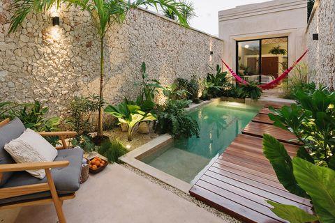 patio interior con paredes de piedra, piscina, vegetación exótica y una hamaca