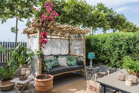 terraza con banco de madera y comedor exterior decorado con plantas