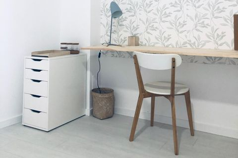 despacho con balda de madera suspendida como mesa y papel pintado botánico en color verde empolvado