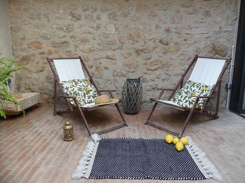 patio rústico con paredes de piedra y dos hamacas