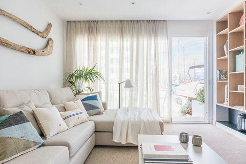 salón decorado en tonos neutros con sofá con chaise longue y estantería de madera