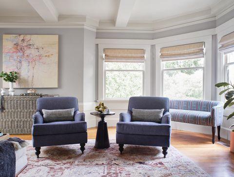 salón con dos butacas clásicas y una mesa auxiliar contemporánea