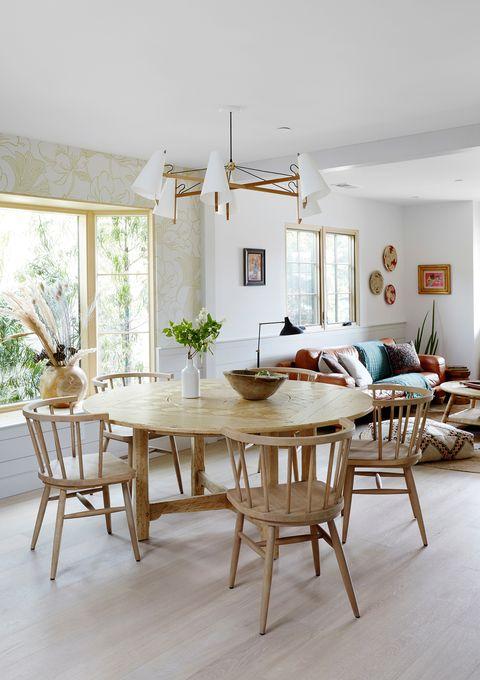 comedor abierto de estilo rústico con mesa redonda y sillas de madera