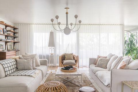 salón decorado en blanco con estilo boho y mid century