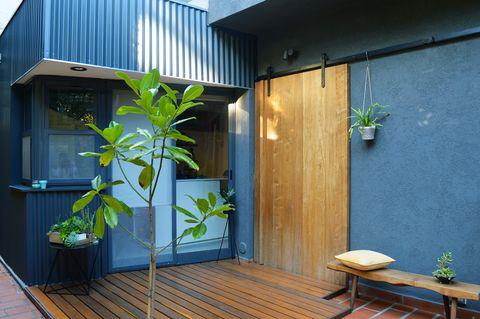 terraza con tarima de madera decorada con plantas y una puerta corredera estilo granero
