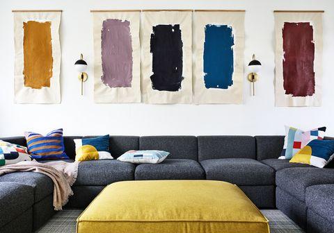 sofá gris modular y obras de arte abstracto en la pared