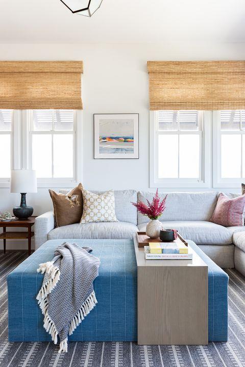 salón con sofá gris, mesa de centro tipo puf tapizada en azul y estores de yute