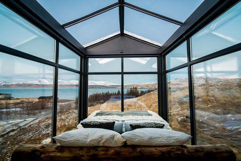 interior de madera de una cabaña de vidrio con cama doble en islandia para ver la aurora boreal