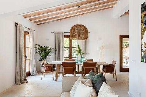 comedor de estilo mediterráneo con textiles blancos y de fibras naturales en una vivienda en mallorca