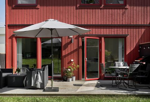 fachada revestida de lamas de madera rojas y terraza de diseño moderno