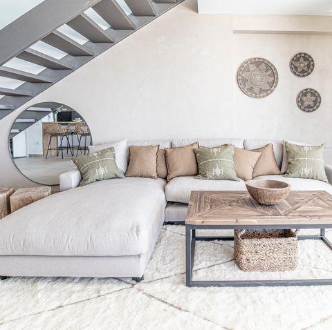 sofá con chaise longue gris, alfombra shaggy y mesa de centro de madera y metal