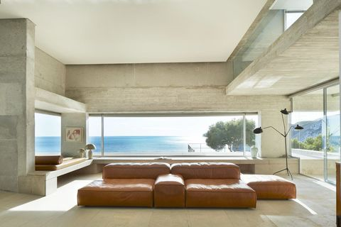 Brown leather modular sofa in brutalist architecture living room with picture windows overlooking Mediterranean Sea