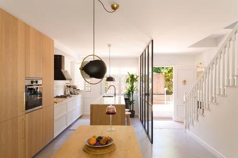 cocina abierta con isla central de madera y cerramiento con perfilería metálica