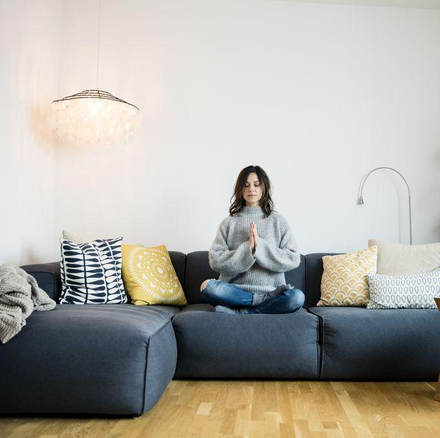 Mujer meditando en el sofá del salón