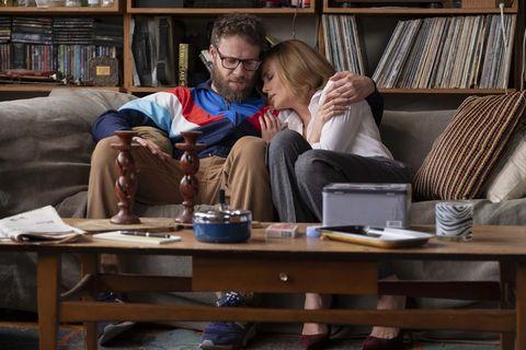 Charlize Theron y Seth Rogen abrazados en un sofá en la películaCasi imposible