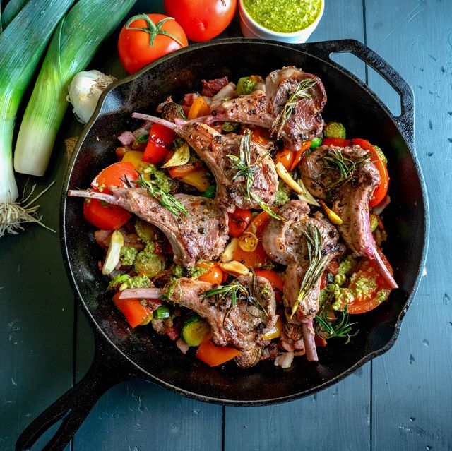 cast iron skillet filled with gourmet lamb chops and a vegetable medley of brussels sprouts, bell pepper, garlic, leeks tomato, garlic and pesto