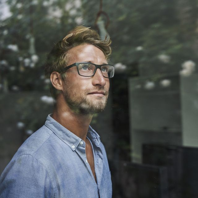 casual young businessman behind windowpane in office