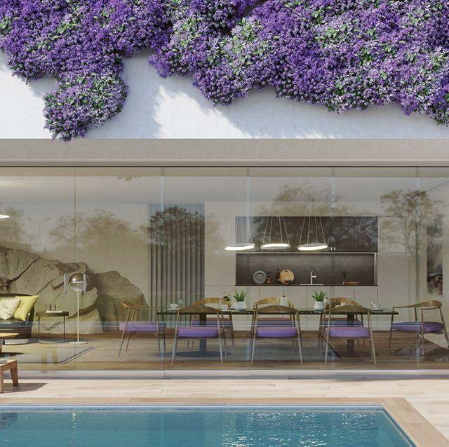 vista de comedor a través de un cerramiento de cristal, de kauma, instalado en la pared exterior de un jardín con piscina