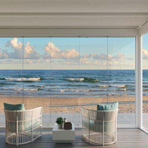terraza con vistas al mar acristalada con cortinas de cristal del nuevo catálogo de cerramientos kauma