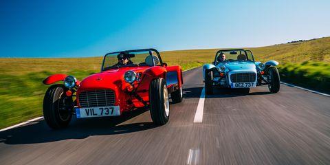 caterham seven 1600   dos modelos con decoraciones distintas avanzan en paralelo en carretera vista frontal