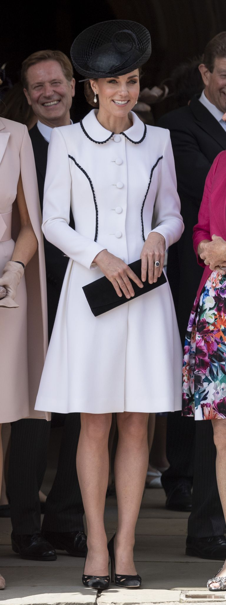 Kate attended the Order of the Garter ceremony wearing a white collared Catherine Walker coat dress with black piping, a black hat, pearl earrings, and black pumps. The Duchess was joined by the Queen, Prince William, Prince Charles, and other members of the royal family for the service.