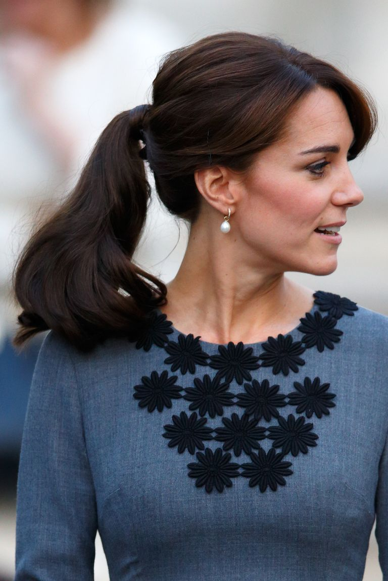 Duchess Kate left her long bangs loose for this preppy style, and wrapped a strand of hair around the ponytail to disguise the hair tie.