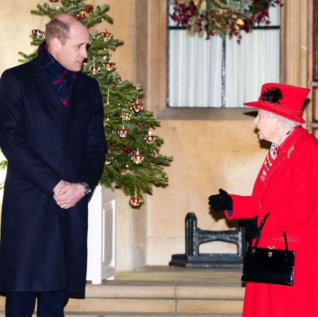 the queen decorates her outdoor christmas tree with mini red crowns