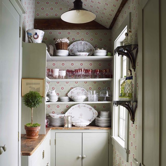 a butler's pantry walls are covered in a recolored historic parisian pattern open shelves are filled with glasses and dishware