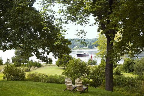 a grassy waterfront with trees and two adirondack chairs there's a boat in the river