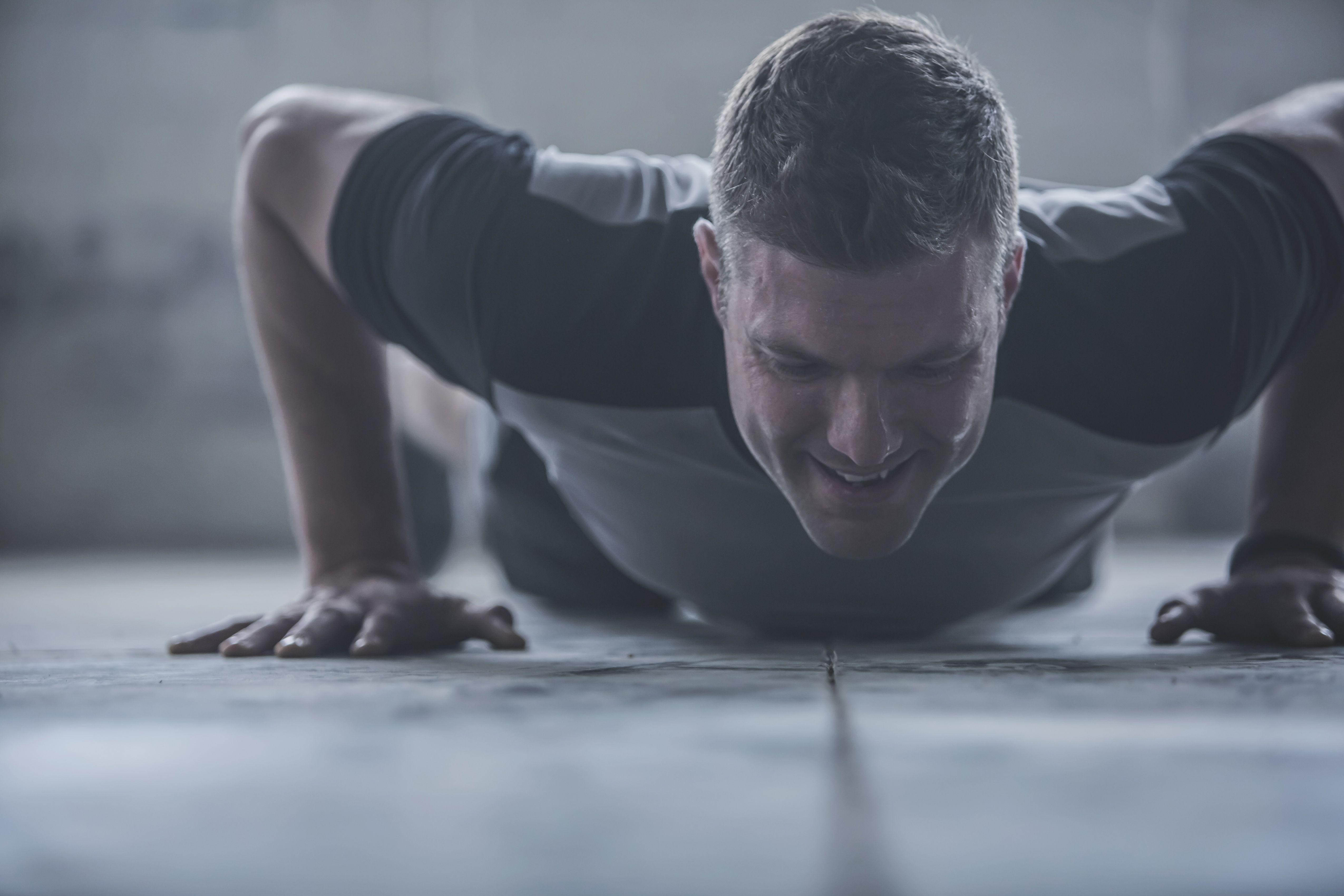 Caucasian athlete doing push-ups on floor