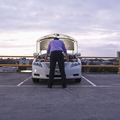 caucasian businessman checking underneath automobile hood
