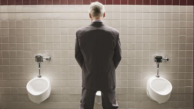 caucasian businessman using public restroom