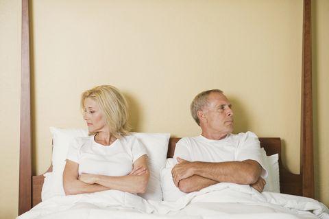 Caucasian couple arguing in bed