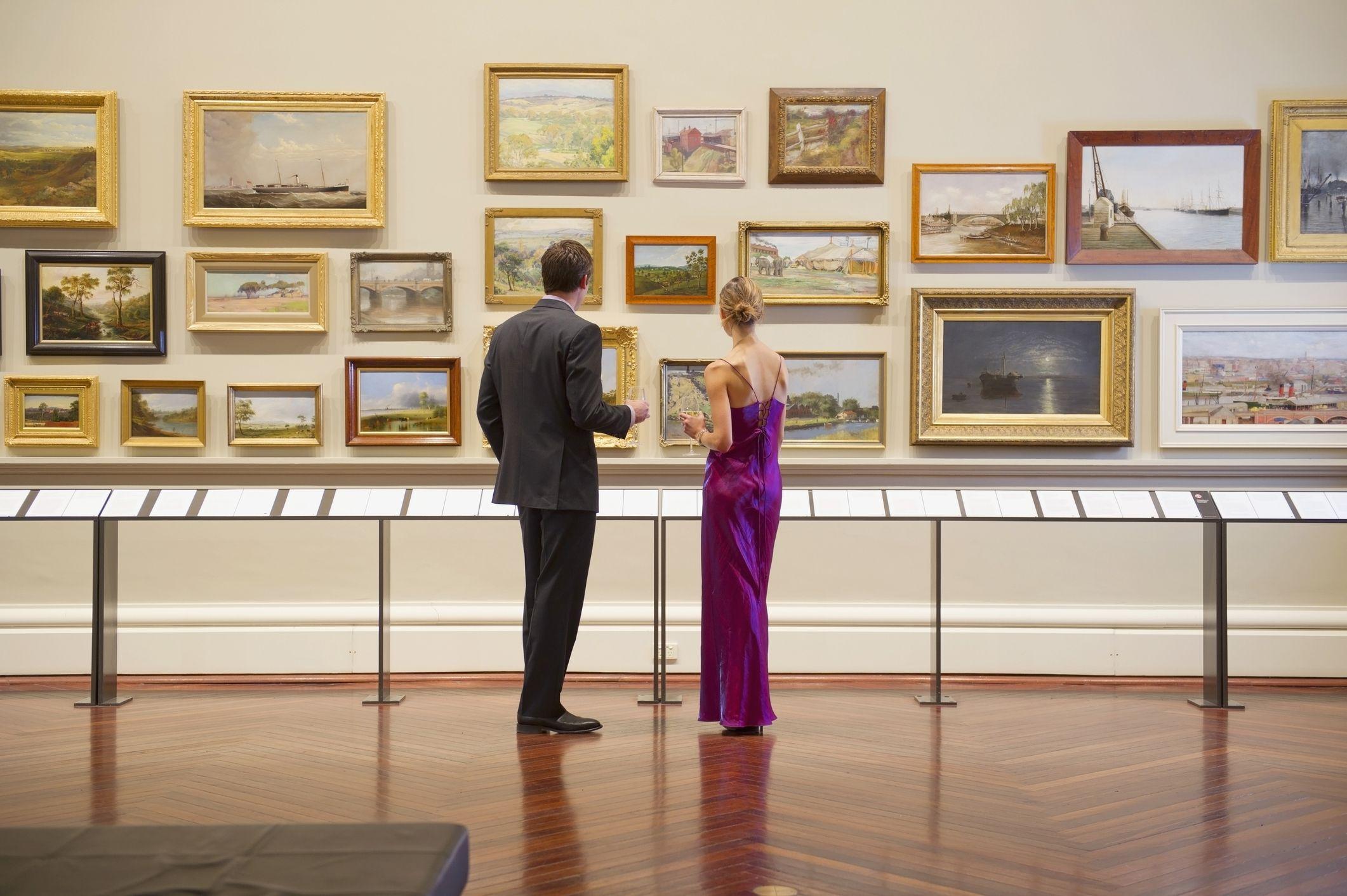 кавказка двойка вечерно облекло, възхищавайки се на изкуството в музея