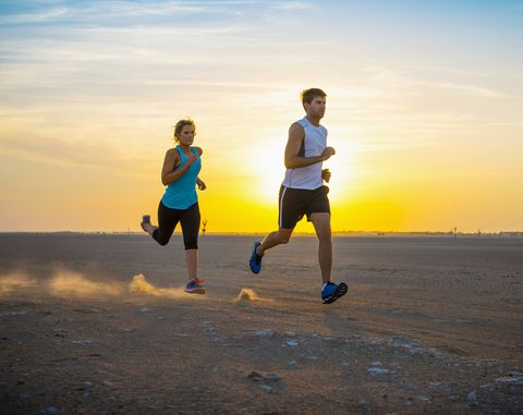 Caucasian couple running in desert
