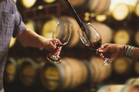 Caucasian couple tasting wine in cellar