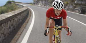 Caucasian cyclist cheering on remote coastal road