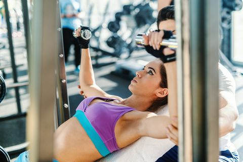 Caucasian dedicated woman in sportswear lying on bench and lifting dumbbells while her personal trainer helping her. Gym interior.