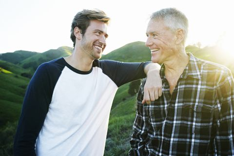 caucasian father and son smiling on rural hilltop