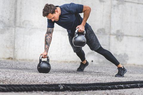 caucasian male athlete doing kettlebell plank row exercise
