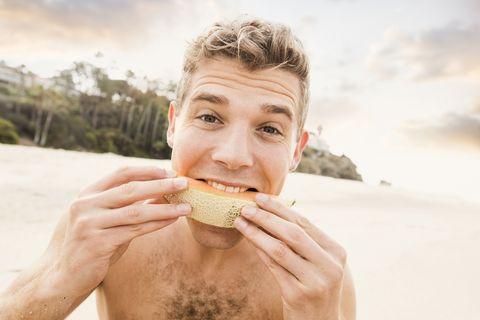 Caucasian man eating fruit on beach