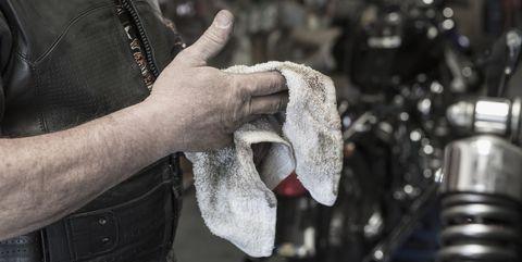 Caucasian man repairing motorcycle wiping hands