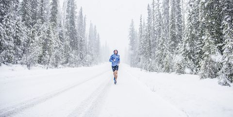 Caucasian man running on snowy forest road