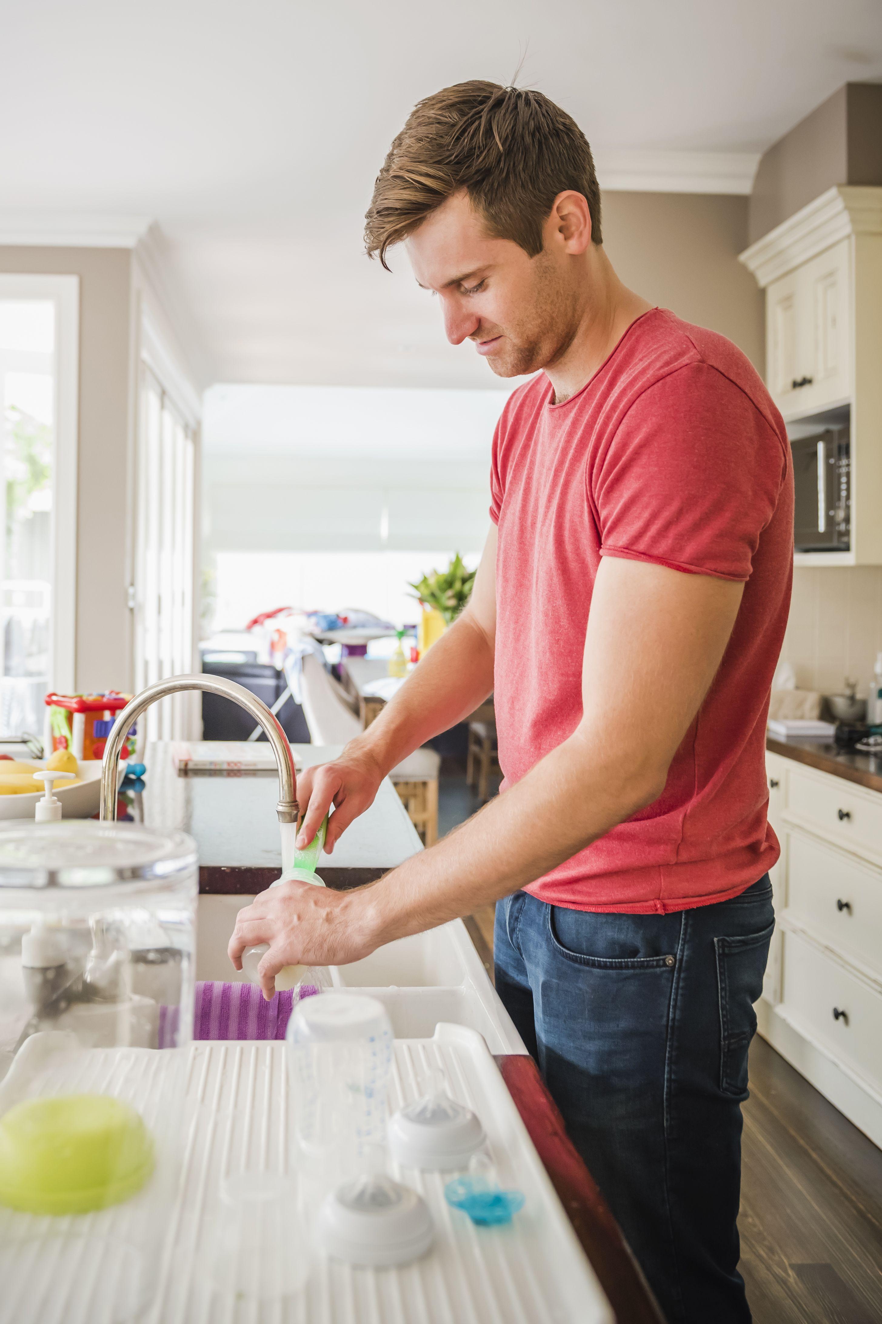Caucasian man washing baby bottle