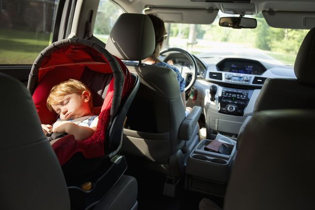 caucasian mother driving car with baby son in car seat