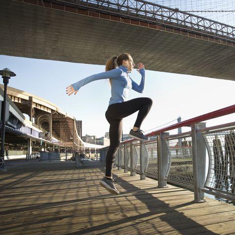Caucasian runner stretching on waterfront, New York, New York, United States