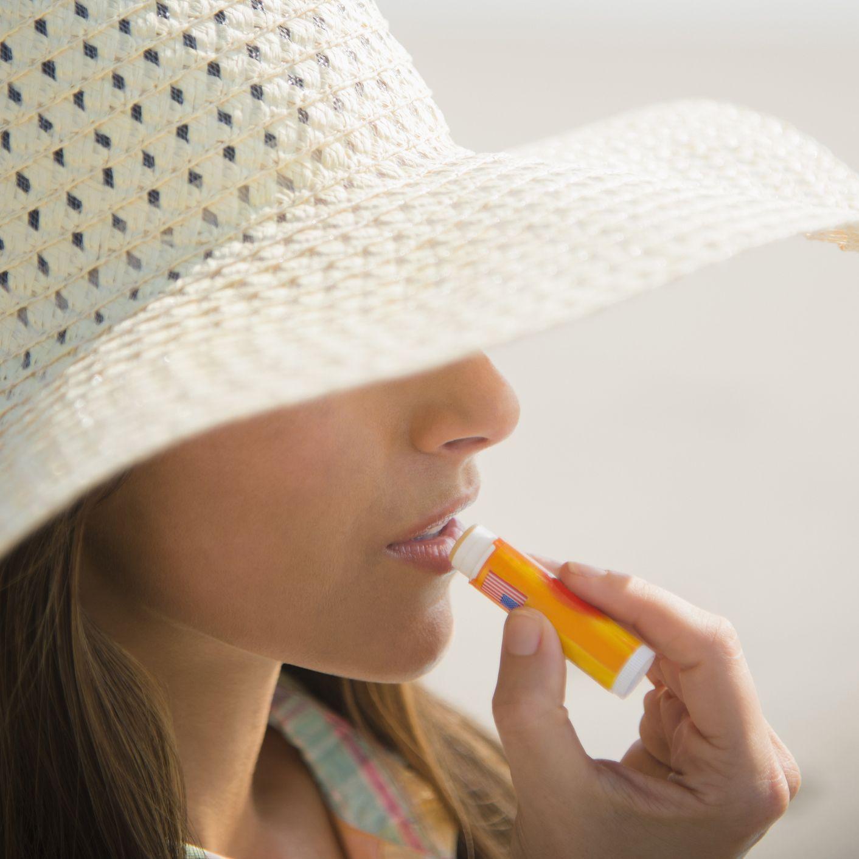 applying sunscreen lip balm at beach