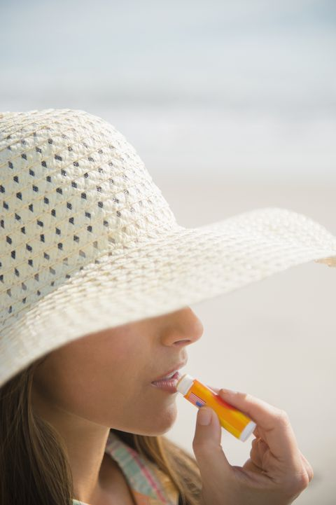 Caucasian woman applying sunscreen lip balm at beach