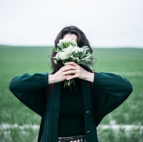 caucasian woman holding wildflowers in front of face