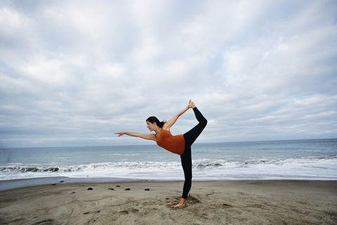Caucasian woman performing yoga on beach